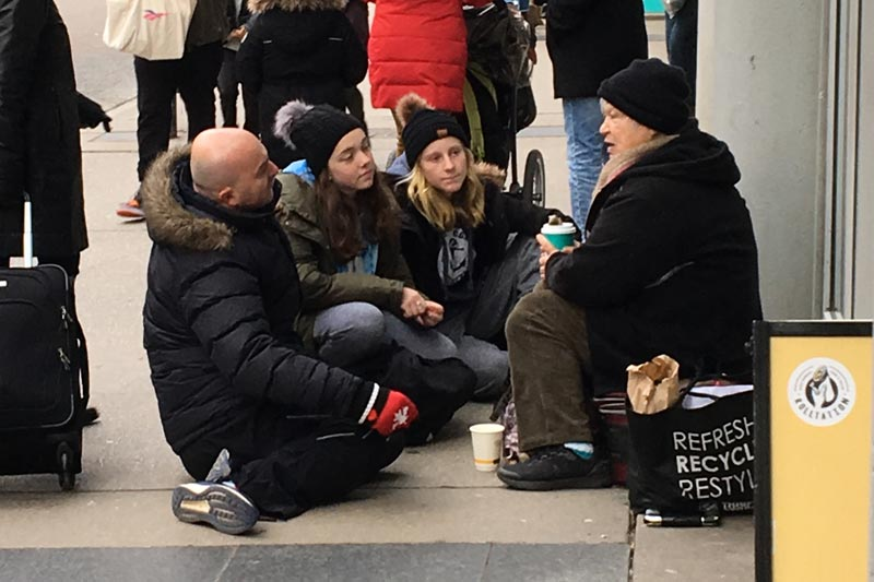Group talking to homeless woman